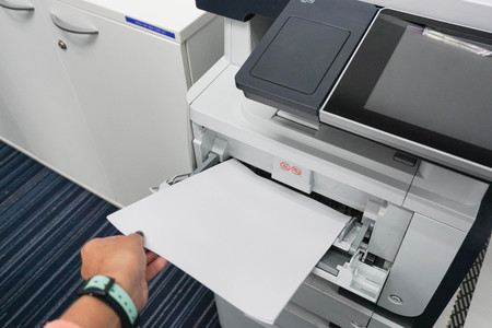 Pull paper from the printer in the office Stock Photo
