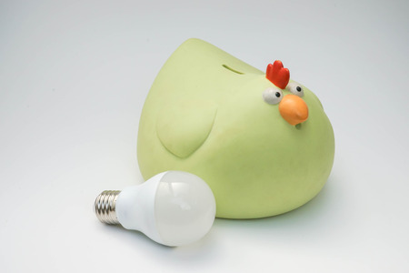 Green piggy bank with LED bulb in white background Stock Photo