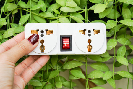 hold a white plug socket with nature background for using energy economically Stock Photo