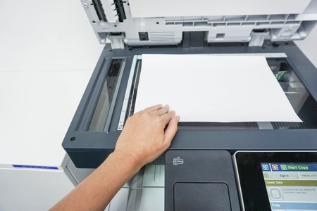xerox: woman scan a document by the printer in the office