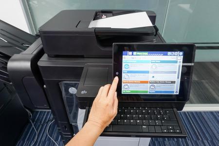 vrouw drukt op de printer touchscreen om documenten te scannen