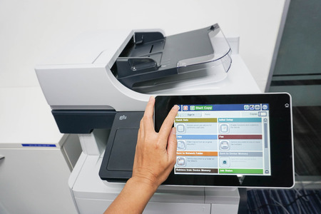 xerox: woman use touch screen of printer for copying documents