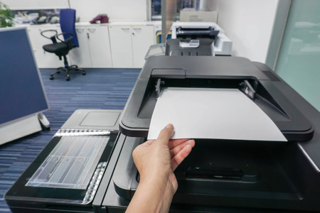 Businesswoman put paper sheet into printer machine