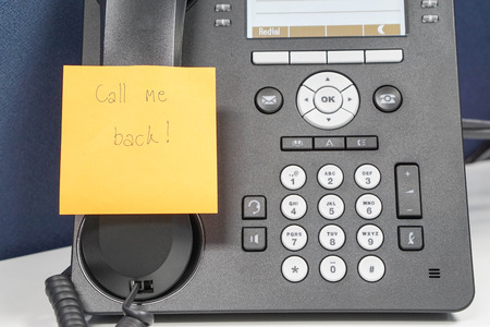 adjuntar: close up message on sticky note of calling back attach on IP phone Foto de archivo