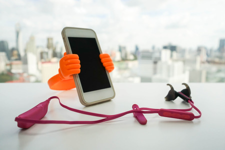 earphone: smartphone with holder stand with pink wireless earphone