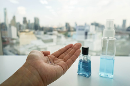 left hand: alcohol bottle and anti-bacterial hand gel on woman left hand