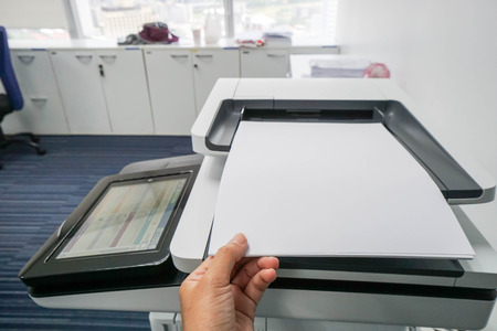 secretary tray: businesswoman put mock up A4 paper sheet on printer feed for scanning