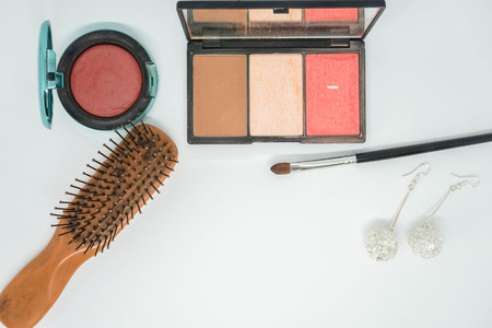 isolated cosmetics, brush on and comb with earrings for beauty