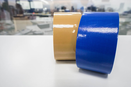 close up roll of dark blue and brown adhesive tapes in office for postal