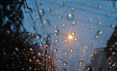 windows: rain water with street light bokeh on car wind shield after raining