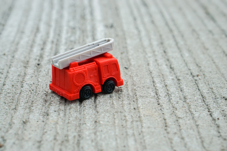 red electricity and utility service truck model toy on concrete floor