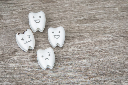 mondgezondheidspictogram - schattige gezonde en huilende rotte tanden op hout Stockfoto