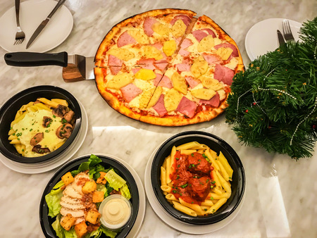 top view of Hawaiian pan pizza, meatball penne and caesar salad in restaurant