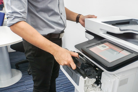Close up businessman in grey shirt put ink toner cartridge into office multifunction printer for printing documents