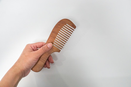 isolated hold wooden comb for hair style Stock Photo