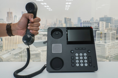 close up businessman hold IP phone handset to call for conference meeting