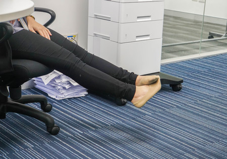 businesswoman take off her shoes to relax on her chair in office