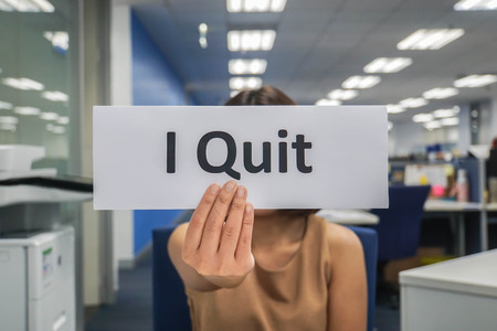 business concept - woman hold paper of I quit in office Фото со стока