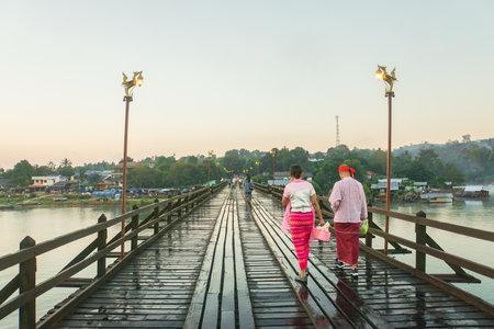 Sangklaburi  Kanchanaburi - 17 December 2017: Mon couple people with traditional dress on wooden bridge in the morning