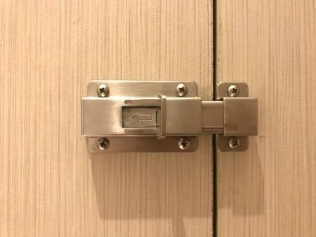 stainless door bolt on the wooden toilet door Banco de Imagens