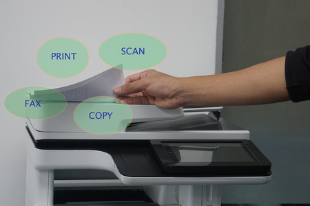 close up man with paper on multi functional printer to print, scan, copy and fax in office