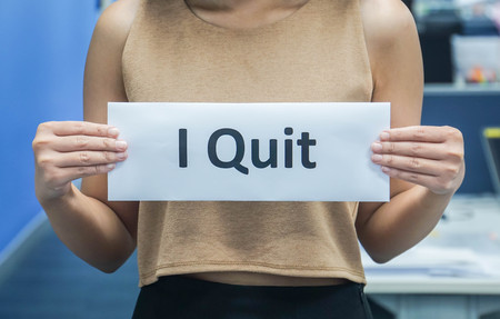 businesswoman hold I quit as a resignation letter with both hands in office 스톡 콘텐츠