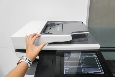 close up businesswoman use multi function printer to scan documents in office