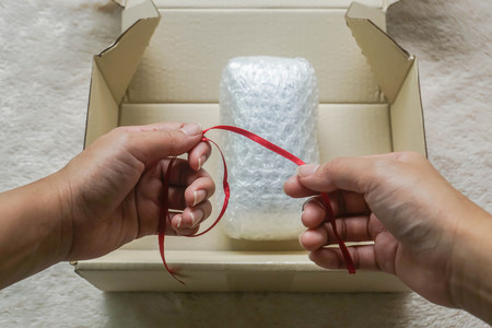 close up woman hold red ribbon as bow for gift in bubble sheet in box