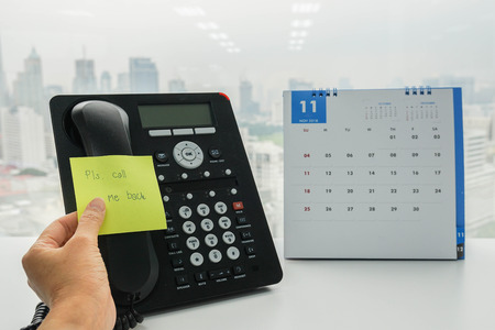 close up businesswoman put a note of call me back on colleague IP phone