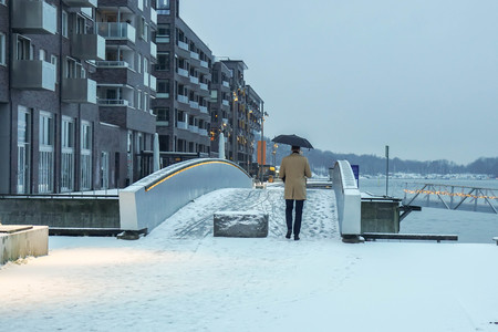 man in winter coat with umbrella in snow fall day in Oslo, Norway Stockfoto