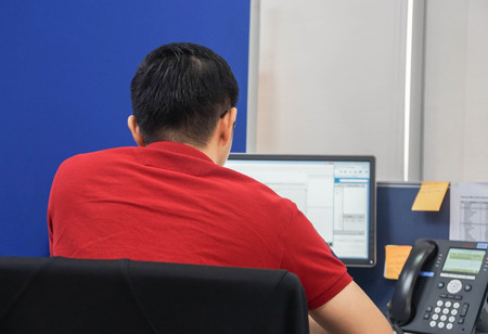 man wearing eyeglasses with red shirt use PC computer in office during working
