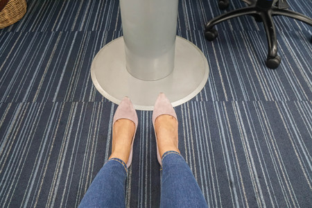 close up woman legs wear blue jeans with purple high heel sits in meeting room Фото со стока