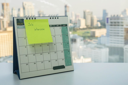 sticky note with job interview reminder on November calendar