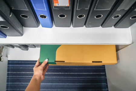 secretary pull classified business paper box from office cabinet