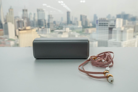 wireless portable speaker and  cute pink earphone on office desk Stockfoto
