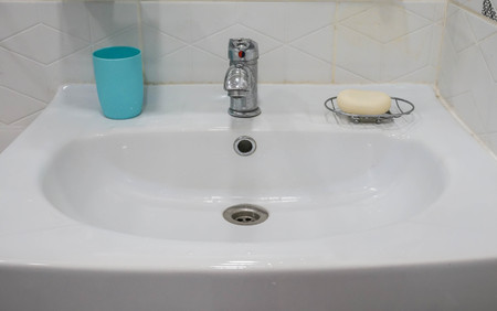 white ceramic sink in bathroom with plastic glass for brush and soap for hand cleaning