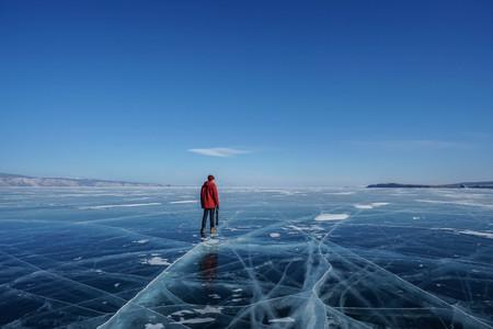 man in winter jacket travel holding camera tripod on frozen Baikal lake in Irkutsk, russia in February