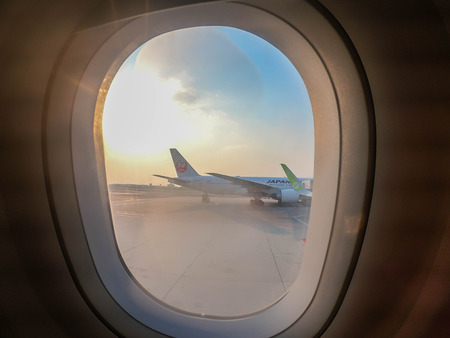 Bangkok  Thailand - 12 February 2019: passenger window shade in airplane to see Japan Airlines and S7 aircrafts Фото со стока