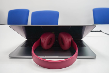 close up cute pink wireless headphone on notebook computer in office meeting room Фото со стока