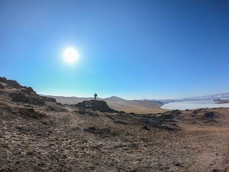 explore the world concept - man traveler on mountain peak in Baikal with sunny blue sky