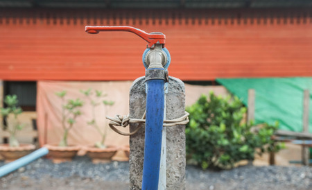 old vintage water tap with rubber tube at rural house Фото со стока