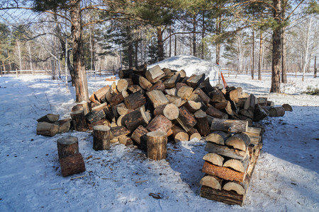 piles of firewood on snowy ground in winter for fireplace and warmth for living at home Фото со стока