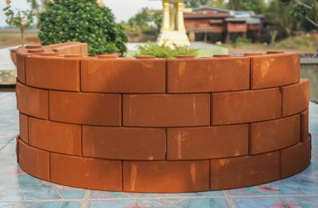 stacks of vintage orange brick for flower pot outside the house Фото со стока