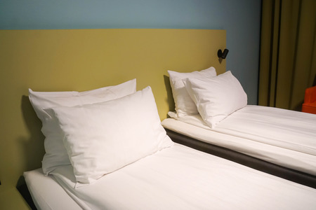 white mattress and comfortable pillows in hotel twin bedroom