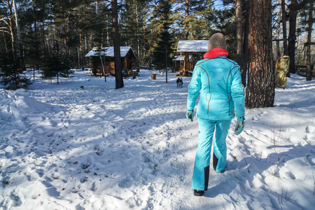 woman with knitted wool hat and blue winter coat walk on snow going to wooden cabin in forest