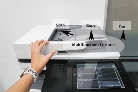words detailing the printer function on close up employee use office printer machine for scanning, copying and sending fax business documents Imagens