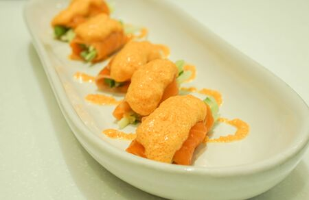 close up shot of salmon asparagus roll with spicy sauce