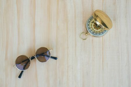 explorer and holiday concept of round brown sunglasses for summer outdoor activities with compass Stock Photo