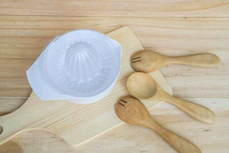 juice hand squeezer in chopping board and wooden spoon and fork in kitchen Stock Photo