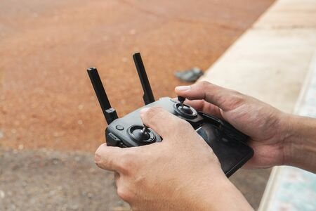 close up man play Drone by remote control joystick with smartphone at home as hobby